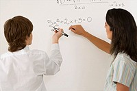 Rear view of a teenage boy solving algebra on whiteboard and a female teacher standing beside him
