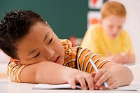 Close_up of a schoolboy resting on a desk with another schoolboy sitting in the background in a classroom