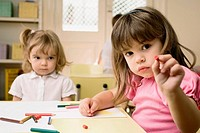 Portrait of a girl showing a crayon with her friend sitting in the background