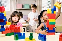 Two girls playing with plastic blocks with their friends in the background (thumbnail)