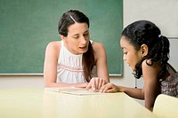 Female teacher teaching her student in a classroom