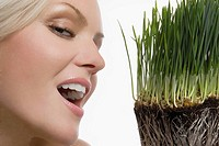 Close_up of a young woman smiling with wheatgrass in front of her face