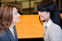Close_up of two businesswomen smiling