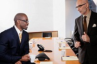 Two businessmen discussing in a conference room