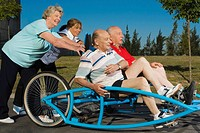 Two senior men sitting on a quadracycle and two senior women pushing it