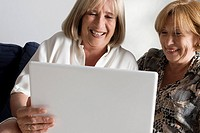 Two senior women looking at a laptop