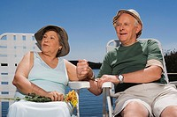 Senior couple sitting at the lakeside with holding hands of each other