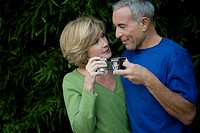 Close_up of a senior man with a mature woman holding tea cups and looking at each other