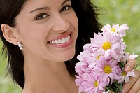 Portrait of a young woman holding a bouquet of flowers and smiling (thumbnail)
