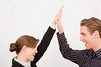 Businessman and a businesswoman giving high_five and smiling