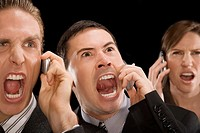 Close_up of business executives shouting on a mobile phone