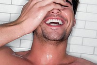 Close_up of a young man bathing and laughing