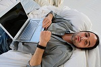 High angle view of a young man lying on the bed and a laptop on his stomach