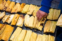 High angle view of a man roosting tamales on a barbecue grill, Zacatecas State, Mexico