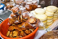 Breads and stacks of cheese at a market stall, Zacatecas State, Mexico