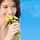 Close_up of a young woman holding flowers and smiling