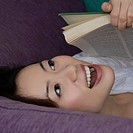Close-up of a young woman holding a book and laughing (thumbnail)