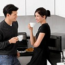 Young couple holding their coffee cups in the kitchen and smiling