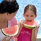 Close_up of a young woman and her daughter eating watermelon
