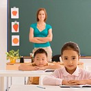 Schoolgirl sitting in a classroom with a schoolboy and a female teacher in the background
