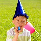 Portrait of a boy blowing a party horn blower (thumbnail)