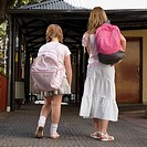 Rear view of two schoolgirls carrying schoolbags and walking