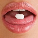 Close_up of a pill on a young woman's tongue