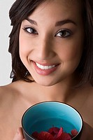 Portrait of a young woman holding a bowl of water with floating leaves