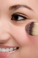 Close_up of a young woman applying make_up and smiling