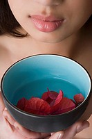 Close_up of a young woman holding a bowl of water with floating leaves