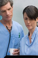 Male surgeon and a female surgeon looking at a medical record