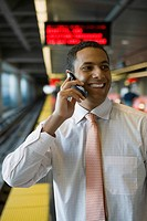Close_up of a businessman talking on a mobile phone at a subway station