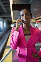 Close_up of a young woman talking on a mobile phone at a subway station