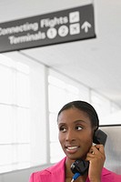 Close_up of a businesswoman talking on a pay phone and smiling