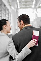 Rear view of a businesswoman and a businessman looking at each other at an airport