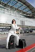 Businesswoman sitting on a suitcase and waiting for a taxi outside an airport