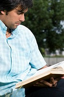 Close_up of a young man reading a book