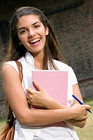 Portrait of a young woman holding a book and smiling