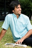 Close_up of a young man sitting on grass and smiling