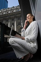 Side profile of a businesswoman talking on a mobile phone and using a laptop