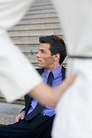 Businessman sitting on steps and looking away
