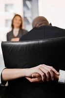 Close_up of a man's hand holding a woman's hand behind a chair in an office