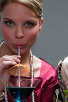 Portrait of a young woman drinking cocktail (thumbnail)