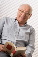 Close_up of a senior man reading a book and smiling