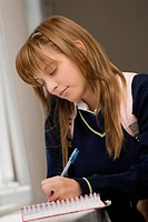 Close-up of a teenage girl writing in a spiral notebook (thumbnail)