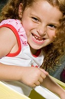 Close_up of a girl in a toy car and smiling