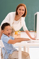 Portrait of a schoolboy with his female teacher in front of a computer