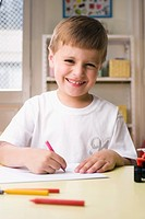 Portrait of a boy drawing on a sheet of paper and smiling