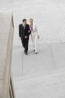 Businessman and a businesswoman walking with their arm in arm