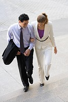 Businessman and a businesswoman moving up on steps with their arm in arm